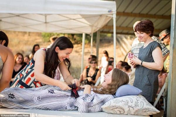 "This July 24, 2016 photo provided by Niels Alpert, Amanda Friedland, left, surrounded by friends and family adjusts her friend Betsy Davis's sash as she lays on a bed during her ""Right To Die Party"" in Ojai, Calif. In early July, Davis emailed her closest friends and family to invite them to a two-day celebration, telling them: ""These circumstances are unlike any party you have attended before, requiring emotional stamina, centeredness, and openness. And one rule: No crying."" The 41-year-old woman diagnosed with ALS, held the party to say goodbye before becoming one of the first California residents to take life-ending drugs under a new law that gave such an option to the terminally ill. (Niels Alpert via AP)"