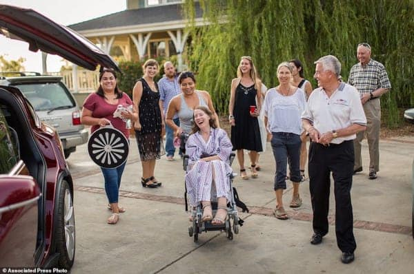 "This July 24, 2016 photo provided by Niels Alpert, Betsy Davis, center, is accompanied by friends and family for her first ride in a friends new Tesla to a hillside to end her life during a ""Right To Die Party"" in Ojai, Calif. In early July, Davis emailed her closest friends and family to invite them to a two-day celebration, telling them: ""These circumstances are unlike any party you have attended before, requiring emotional stamina, centeredness, and openness. And one rule: No crying. "" The 41-year-old woman diagnosed with ALS, held the party to say goodbye before becoming one of the first California residents to take life-ending drugs under a new law that gave such an option to the terminally ill. (Niels Alpert via AP)"