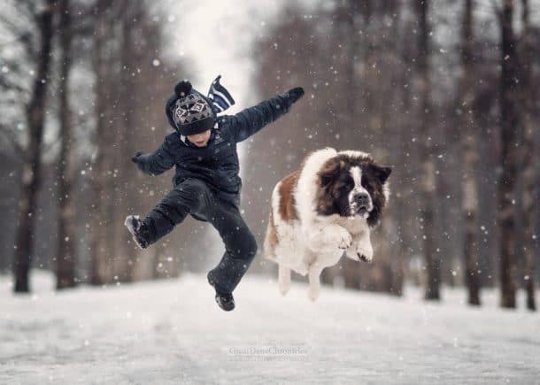Un chien et un garçon qui s'amusent dans la neige