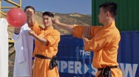 moine Shaolin éclate un ballon derrière une vitre