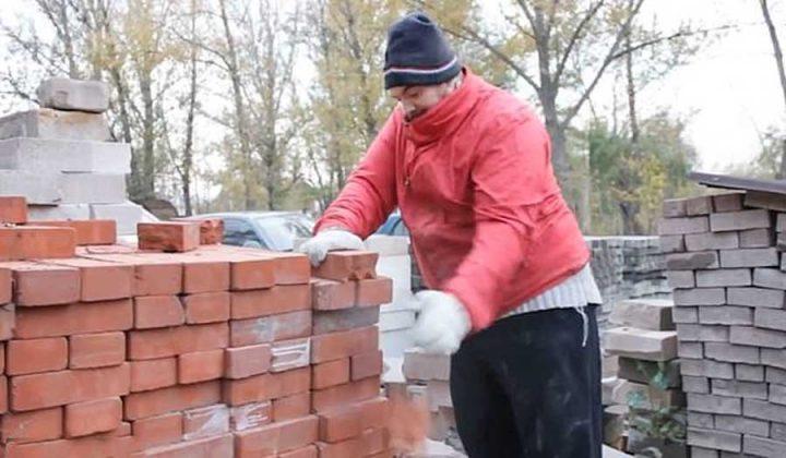 homme casse des briques en deux à la main