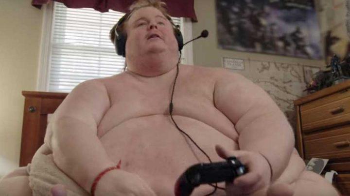 obèse gamer joue nu sur son lit
