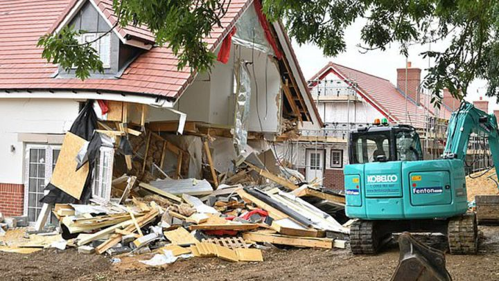 ouvrier démolit des maisons à la tractopelle