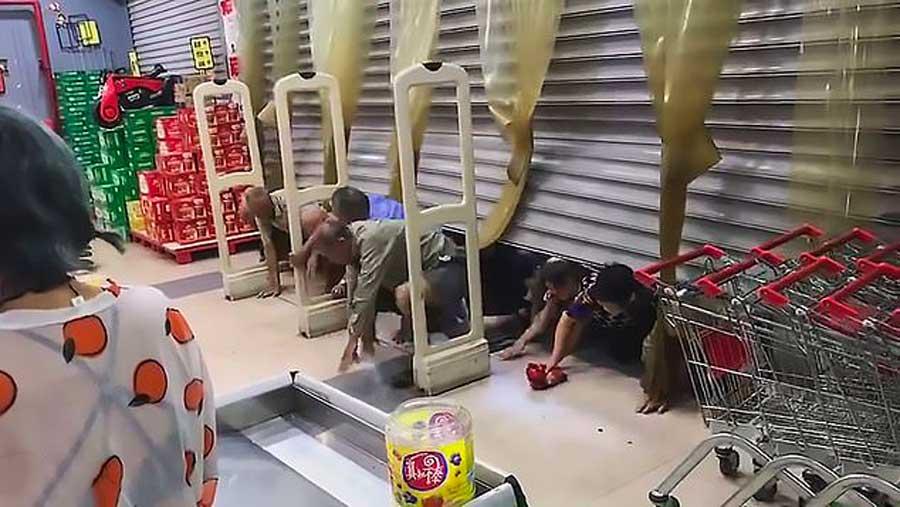 Tels des zombies, des clients rampent sous les grilles d'un magasin qui fait une promo sur les œufs