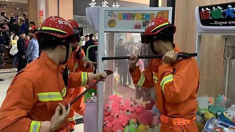Les pompiers démontent une machine attrape-peluche au pied-de-biche pour libérer un enfant coincé à l'intérieur