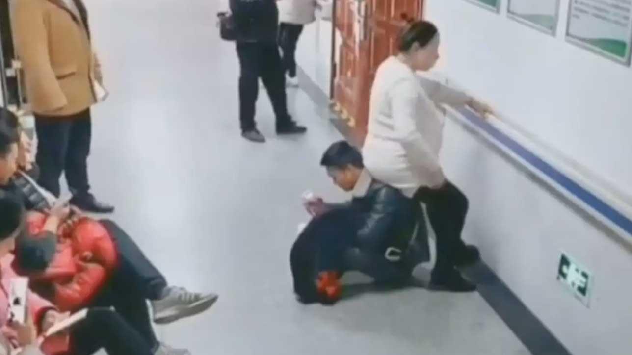 Un homme se couche à terre pour servir de fauteuil à sa femme enceinte qui patiente à l'hôpital