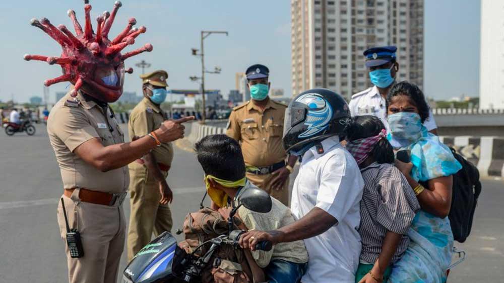 Un policier porte un casque en forme de coronavirus pour sensibiliser la population
