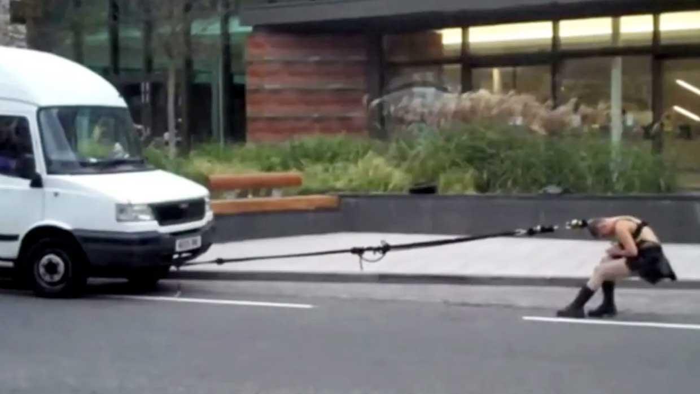 Une femme en panne tire sa camionnette avec ses cheveux jusqu'à la station-essence