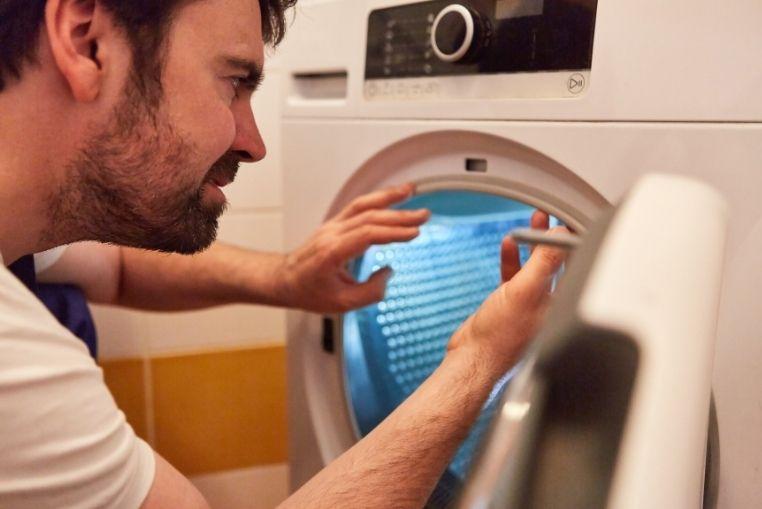Homme qui met des vêtements au sèche-linge